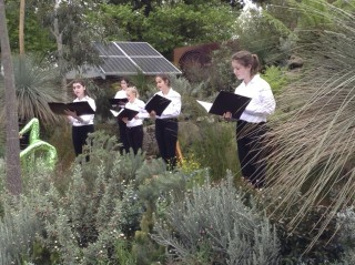 A children's choir singing in the garden